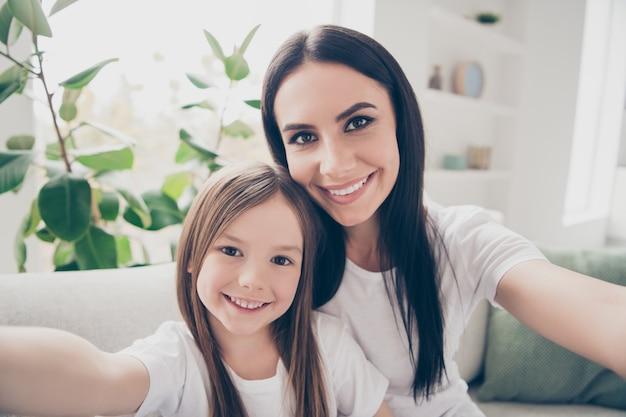 Мама и ее маленькая дочь делают селфи в доме в помещении