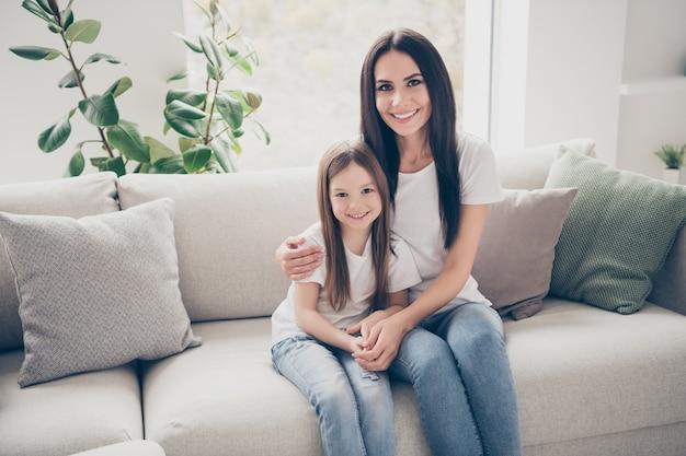 ママと小さな子供は家の中でお互いを抱きしめます