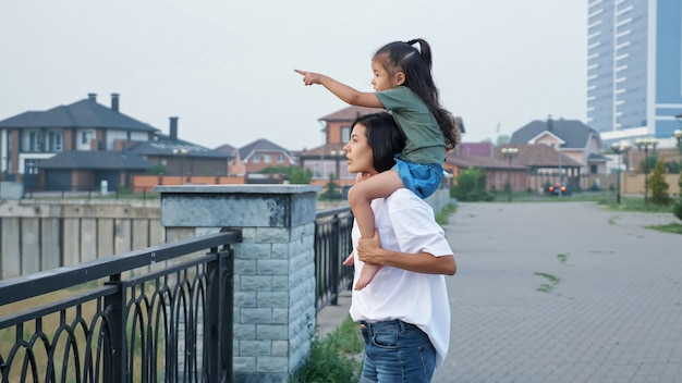 Mommy carries daughter on shoulders walking along embankment