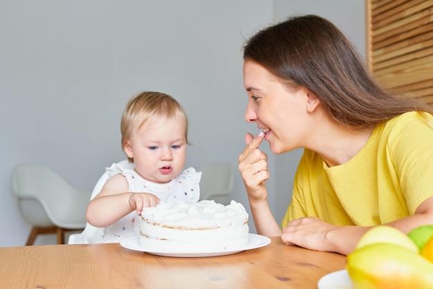 Мама дегустирует сливочный торт, улыбается и смотрит, и любопытный ребенок сидит на стульчике