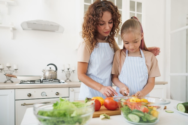 Mommy teaching her teen daughter to cook vegetable salad in kitchen