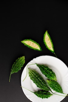 Momordica charanita or bitter cucumber on white plate on black background. copy space, flat lay.