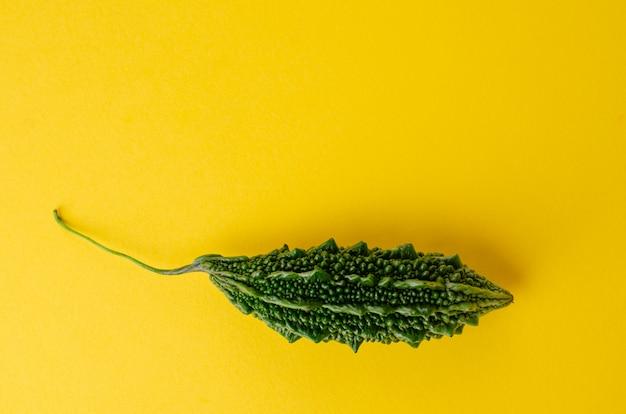 Зрелая горькая тыква или momordica на желтой предпосылке с космосом экземпляра.