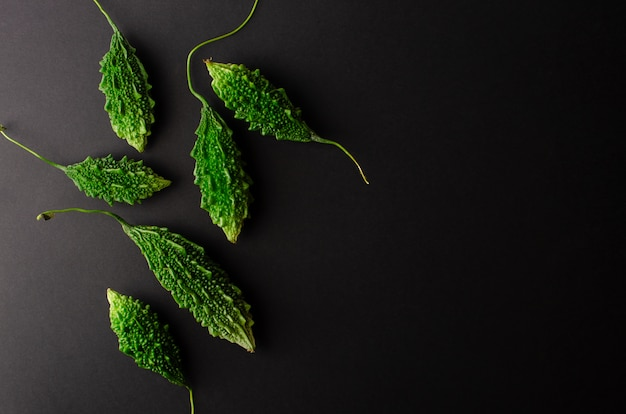 Малая зеленая горькая тыква или momordica на черной предпосылке. плоская планировка, копирование пространства.