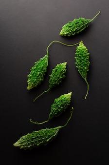 Маленькая зеленая горькая дыня или momordica на черном фоне. плоская планировка, вертикальная.