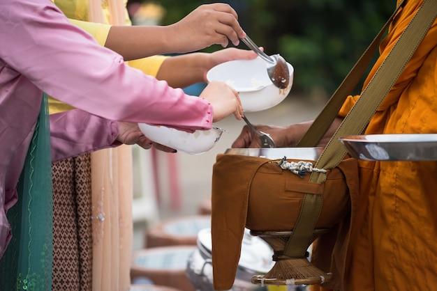 Жители деревни пн и посетители в традиционном костюме предлагают еду чаше для подаяний буддийского монаха.