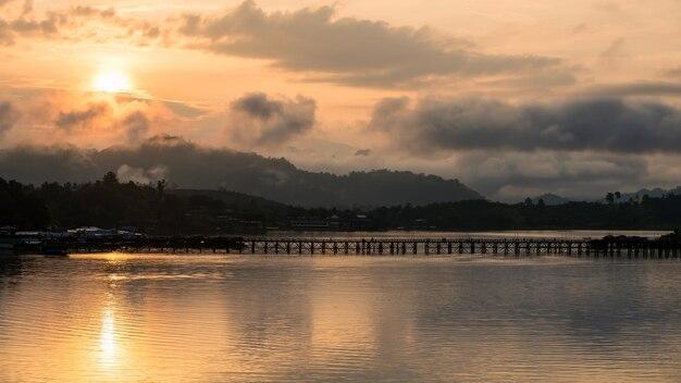 Пн деревянный мост с восходом солнца над горой и туманом в сангхлабури, канчанабури, таиланд