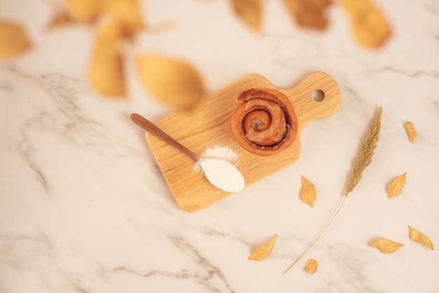 新鮮なベーカリー、白い大理石の表面に木の板に小麦粉の完全なスプーンで新鮮なシナモンmon頭。おいしいおいしいデザート、フランスの朝食。上面図
