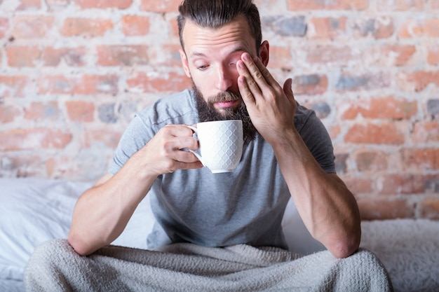 Monday morning again. drowsiness. man sitting in bed with cup of hot drink in hand. rubbing eye, looking distracted.
