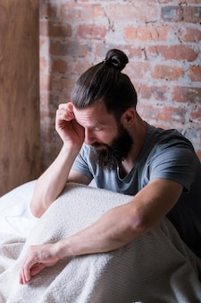 Снова утро понедельника. сонливость. человек сидит в постели. потирает глаза, выглядит усталым и сонным. квартира-лофт.