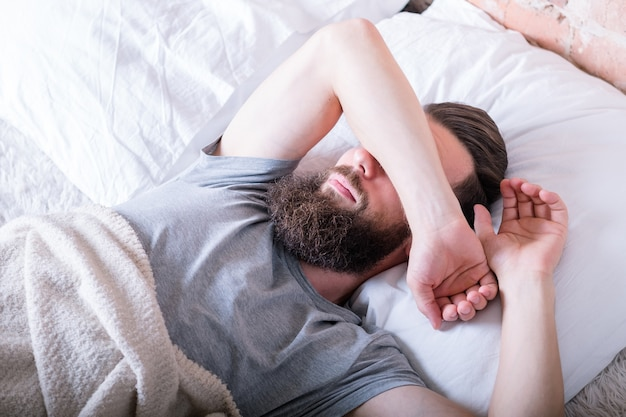 Monday morning again. laziness. man lying in bed covering eyes with arm against daylight.
