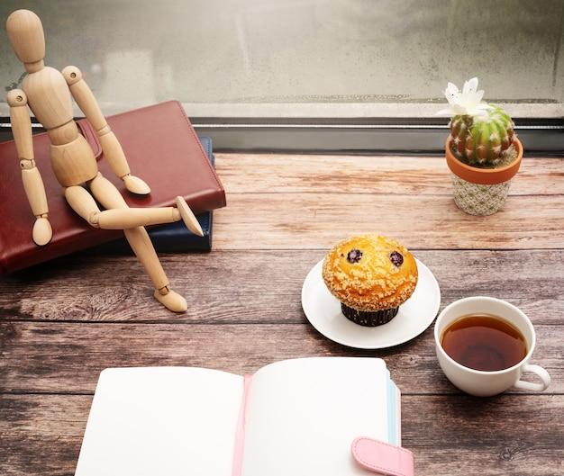 월요일 아침 개념, 창 근처 나무 작업 영역에 뜨거운 차와 머핀 케이크