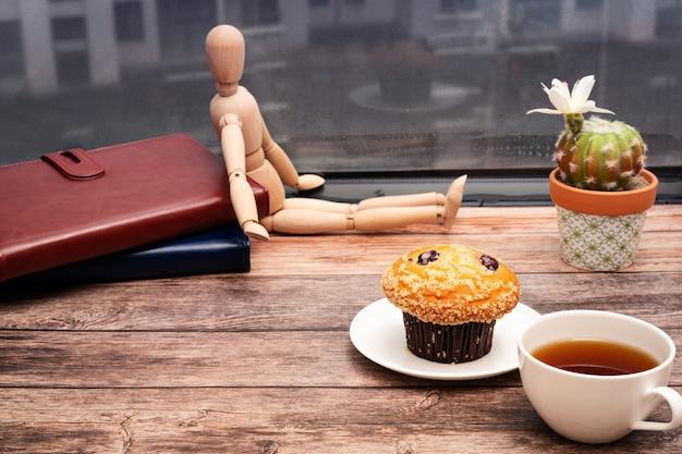 월요일 아침 개념, 나무 작업 영역에 뜨거운 차와 머핀 케이크