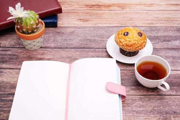Monday morning concept, hot tea and muffin cake on wooden workspace