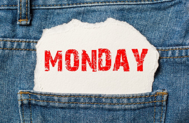 Monday on white paper in the pocket of blue denim jeans