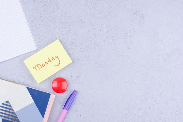 Lunedì che scrive su un adesivo con una spilla rossa da parte