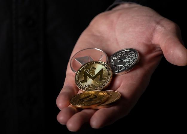 モネロと男性の手に黒い背景のクローズアップの他の異なる暗号通貨コイン