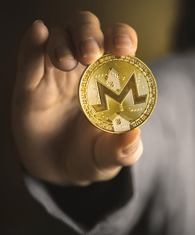 Monero coin in hand close-up view, business background photo of crypto currency