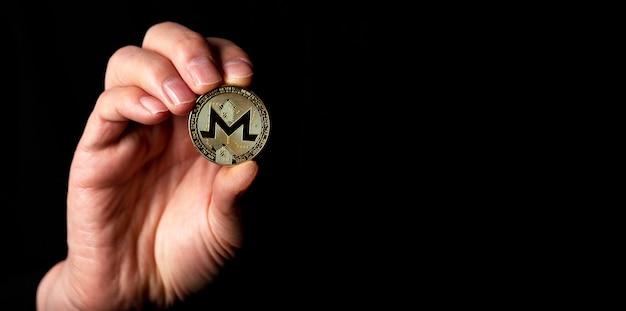 黒の背景に男性の手でモネロ金貨。テキスト用のコピースペースのあるバナー。