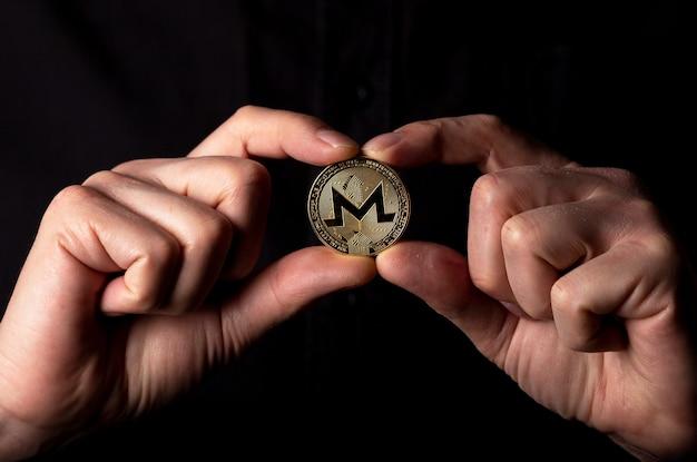 黒の背景に男性の手でモネロ金貨。