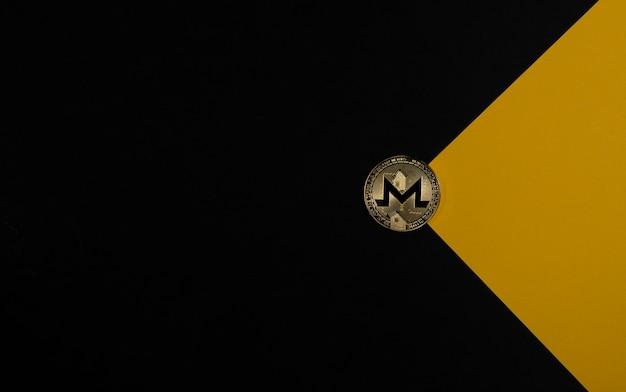 Золотая монета monero на черном и желтом фоне, как конверт с криптовалютой и криптовалютными инвестициями