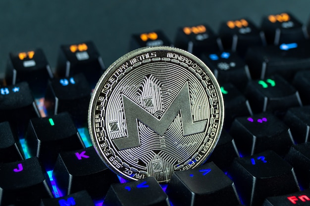 Монета криптовалюты monero крупным планом цветной клавиатуры.