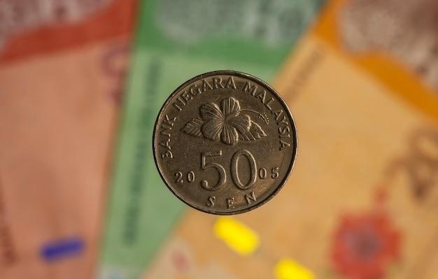 Деньги, монеты 50 сен на размытом фоне банкноты малайзии ринггит, выбранный фокус. бизнес, финансы, экономика и инвестиционная концепция.