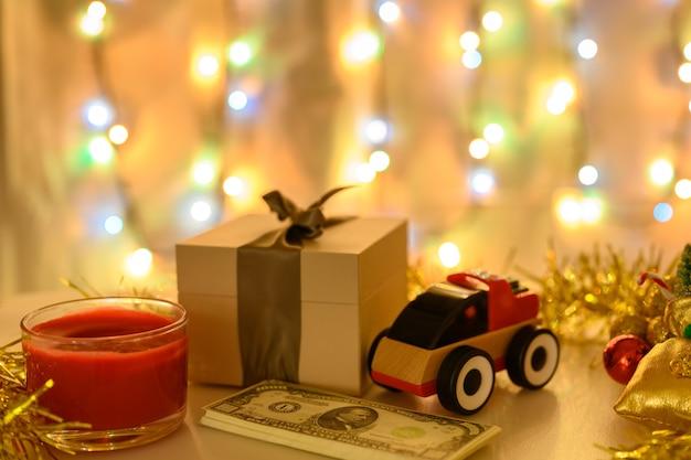 Деньги, коробка с подарком и машинка на новогоднем фоне со светящейся гирляндой в теплых тонах.