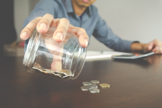 Money accounting concept. businessman check coin in the bottle. management and finance