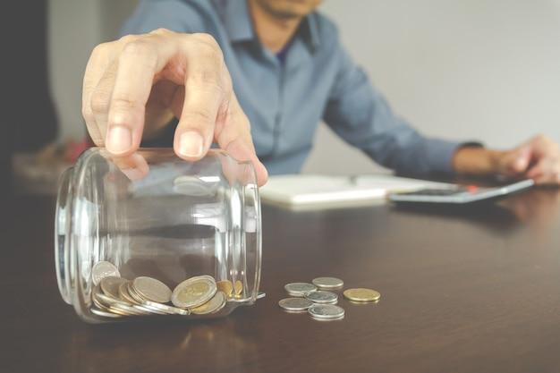 お金の会計の概念。ビジネスマンは、ボトルのコインをチェックします。管理と財務