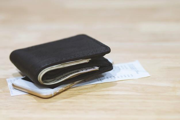 Деньги и кредитная карта в кожаном бумажнике на деревянном столе с мобильным смартфоном и чековой бумагой. покупки онлайн.