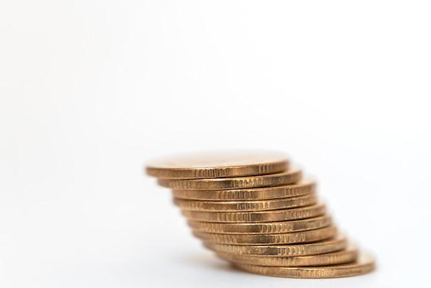 Деньги и финансовая концепция. крупный план стога золотых монет с на белой предпосылке.