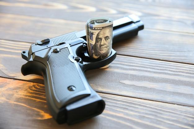 お金と銃は木製の背景に横たわっています。ドルは世界を支配します。堕落した世界。貪欲な殺害。
