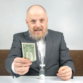ビジネスマンのお金と砂時計。仕事のための時間の分布。決定を下す時間。人間の報酬