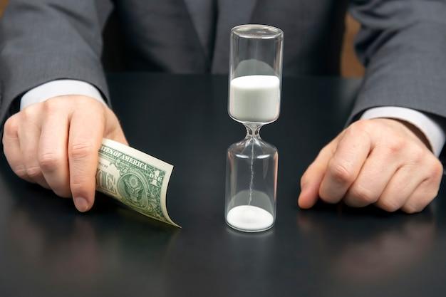 돈과 사업가의 공간에 모래 시계. 작업 시간 분배. 결정을 내릴 시간입니다. 인간의 보수