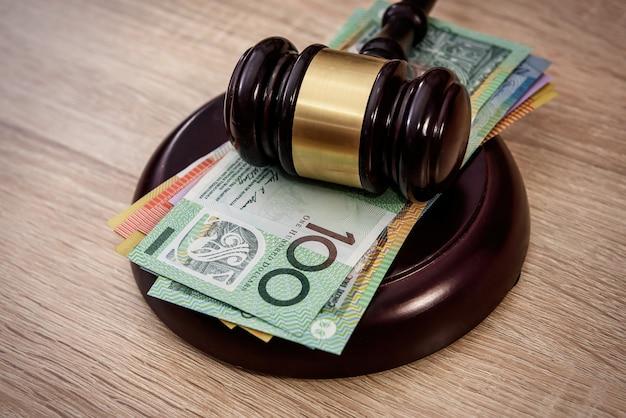 Деньги и справедливость. деревянный молоток судьи с красочными банкнотами австралийского доллара крупным планом