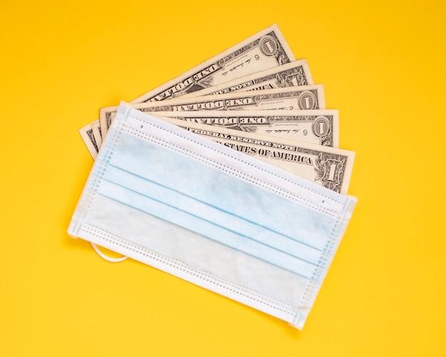 お金とマスクの黄色の背景、covid-19による経済問題