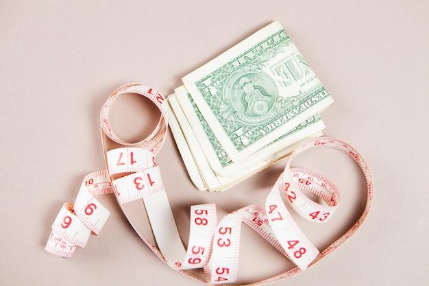 Деньги и метр на белой поверхности