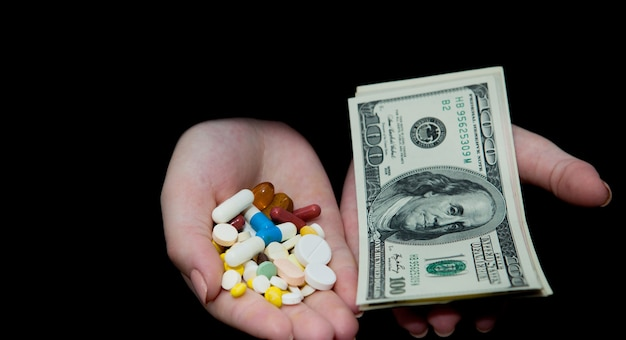 Деньги и таблетки в руках, изолированные на черном