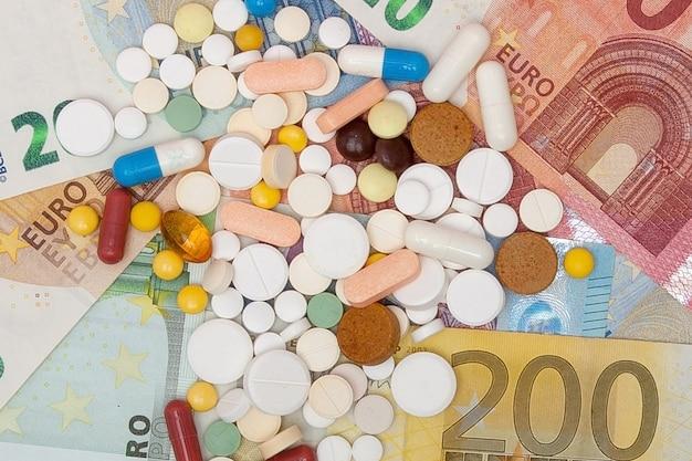 Деньги и таблетки. таблетки разных цветов на деньги. концепция медицины. евро наличными