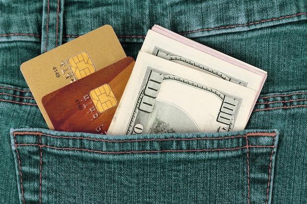 ジーンズのポケットにお金とプラスチックのクレジットカード。ビジネスと金融