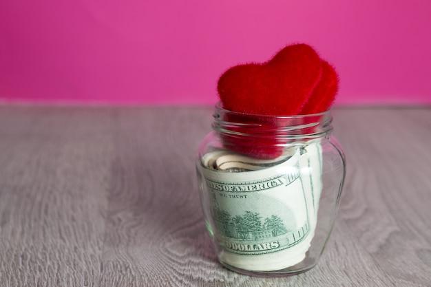 돈과 붉은 마음. 회색 나무 배경에 열린 항아리에 달러. 공간을 복사하십시오. 사랑. 발렌타인 데이.