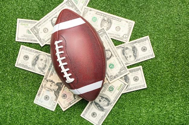 お金とラグビーボール。スポーツ賭博の概念