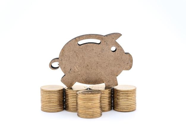 돈과 절약 개념입니다. 흰색 바탕에 금화 더미에 근접 촬영 나무 돼지 저금통 아이콘.