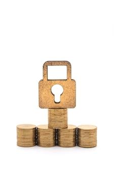 돈과 보안 개념입니다. 흰색 바탕에 금화 더미와 스택이 있는 나무 마스터 키 잠금 아이콘의 클로즈업.