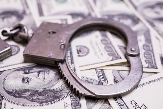 お金と法律、お金の手錠、100ドル札の正面と手錠。ドル、貯蓄、税金、法律の背景をクローズアップ