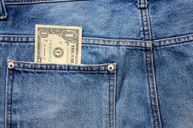 Money in back blue jeans pocket denim texture.
