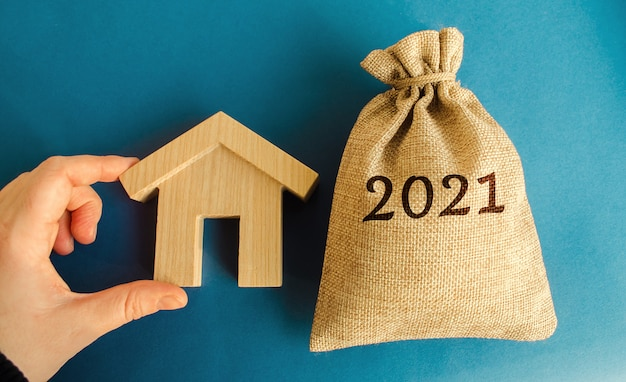 Money bag 2021 and a wooden house real estate concept