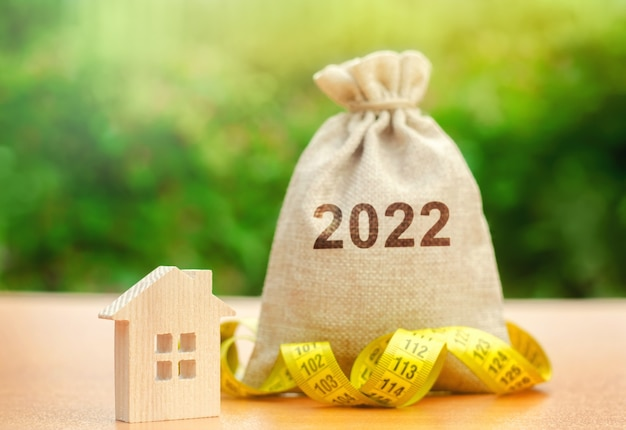 Money bag 2022 and a wooden house real estate concept