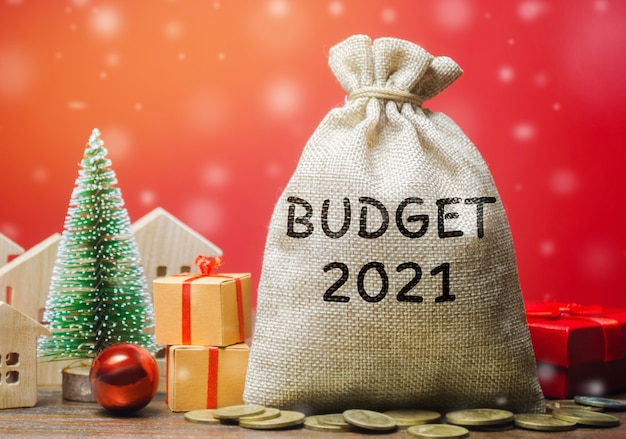 Money bag budget 2021, christmas tree, houses and gifts. accumulating money and planning a budget.